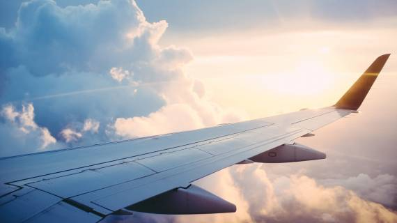 View of airplane wing flying in the sky