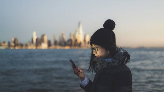 Asian-American woman with mobile phone by the ocean at dusk