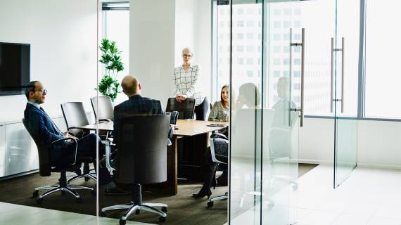 People meeting in a glass-walled room