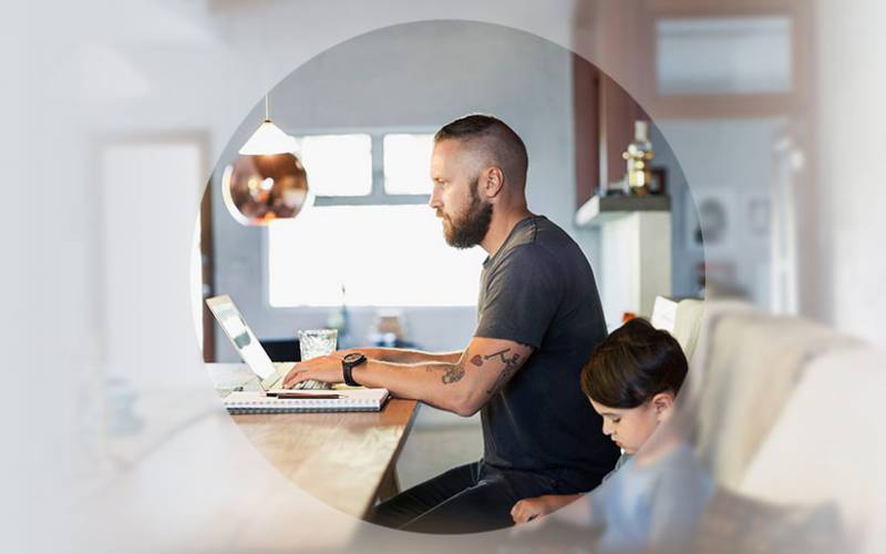 Man working at his computer with his son
